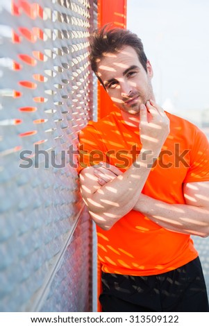 Half length portrait of attractive male runner in fluorescent copy space t-shirt posing to the camera in sunny morning, sports build caucasian men taking break after active training outdoors in city - stock photo