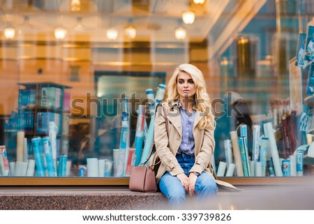 Half length portrait of attractive woman with beautiful blonde hair waiting for someone while sitting alone on a shop sill, charming female tourist enjoying rest after active walking in the fresh air  - stock photo