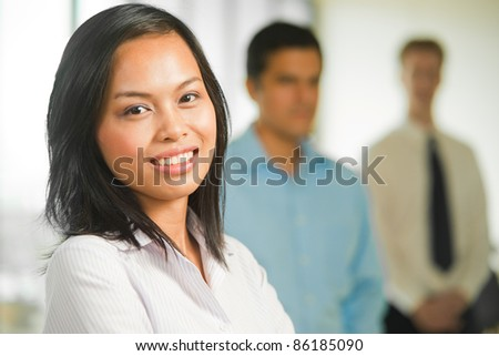 Half length portrait of beautiful Asian business professional standing in front of team of male coworkers behind in a row in background. Horizontal
