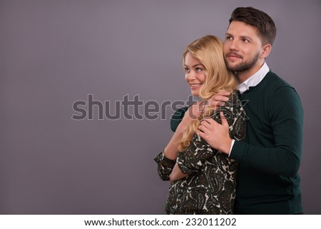 Half-length portrait of beautiful couple standing together aside hugging each other smiling dreaming about their future wedding. Isolated on dark background - stock photo
