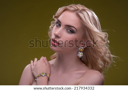 Half-length portrait of beautiful sexy blonde with evening make up wearing great diamond earrings fingering and bracelet putting her hand on her shoulder looking at us isolated on dark background - stock photo