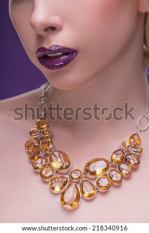 Half-length portrait of beautiful sexy blonde with violet tempting lips and perfect skin wearing precious necklace on her naked shoulders looking at us seductively isolated on violet background - stock photo