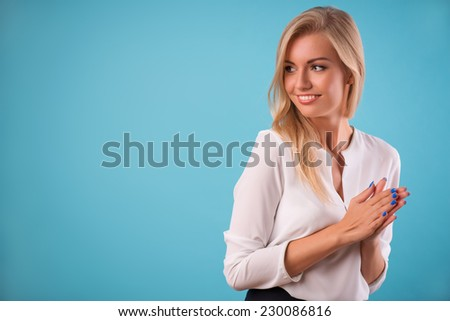 Half-length portrait of beautiful smiling blonde wearing white classic blouse standing aside looking at someone rubbing her hands. Isolated on blue background - stock photo