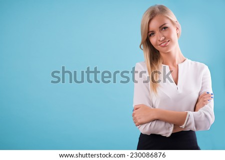 Half-length portrait of beautiful smiling blonde wearing white classic blouse standing aside cross-armed looking at us. Isolated on blue background - stock photo