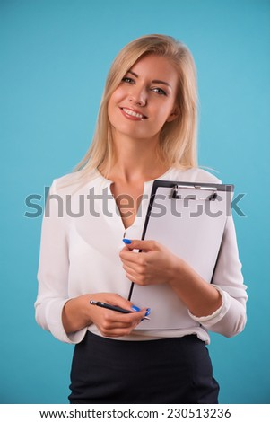 Half-length portrait of beautiful smiling business lady wearing white classic blouse standing looking at us holding in her hands a folder for copy place. Isolated on blue background - stock photo