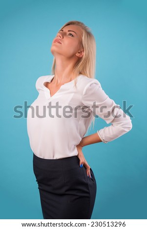 Half-length portrait of beautiful tired blonde wearing white classic blouse and black skirt standing aside having a terrible back pain. Isolated on blue background - stock photo