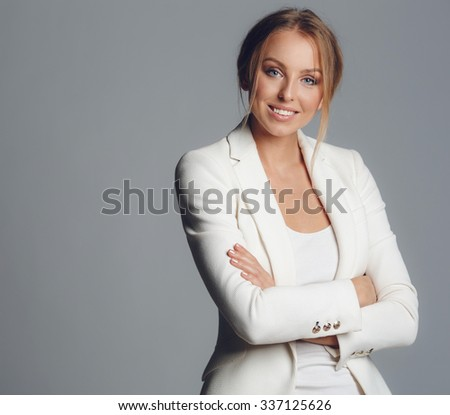 Half-length portrait of business woman with hands crossed, isolated on a white background. Concept of leadership and success. Young sexy blond woman in leather jacket isolated - stock photo