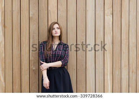 Half length portrait of charming lady thinking about something while standing against copy space area background, young beautiful dreamy woman with good look posing for the camera against wooden wall  - stock photo