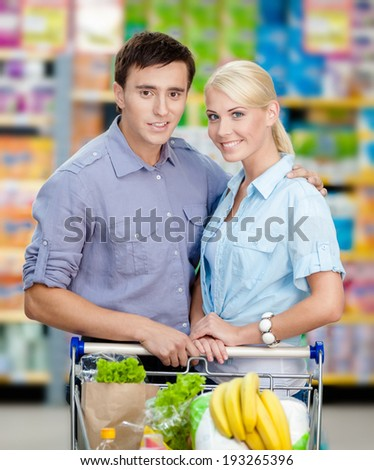 Half-length portrait of couple in the store with cart full of food. Concept of consumerism and healthy food - stock photo