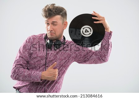 Half-length portrait of excited young DJ with stylish haircut, bow tie posing with vinyl record showing his thumb up as sign OK and winking isolated on white background