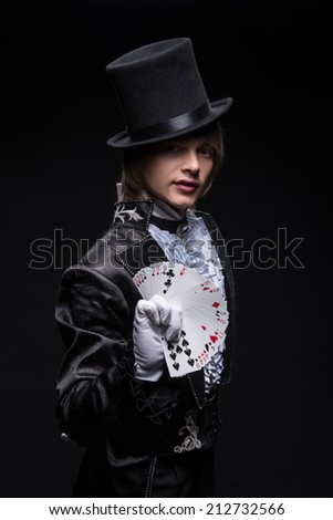 Half-length portrait of fair-haired matchless juggler wearing interesting black costume white shirt and topper showing us the pack of cards in his hand. Isolated on black background - stock photo