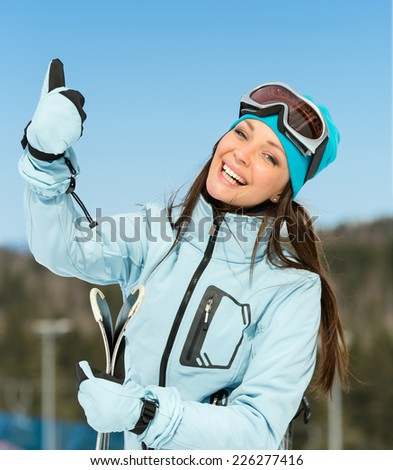 Half-length portrait of female downhill skier thumbing up. Concept of winter sports and cute entertainment