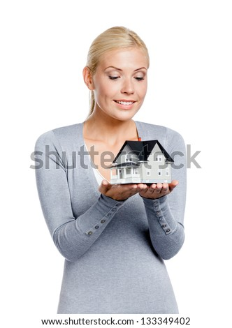 Half-length portrait of female in grey pullover with small model house, isolated on white