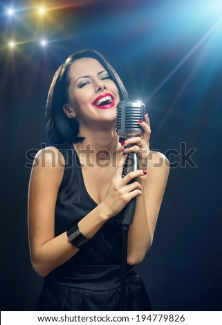 Half-length portrait of female musician with closed eyes wearing black evening dress and keeping mic on illuminated background. Concept of music and retro fashion