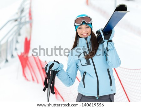 Half-length portrait of female wearing sports jacket and goggles who hands skis - stock photo