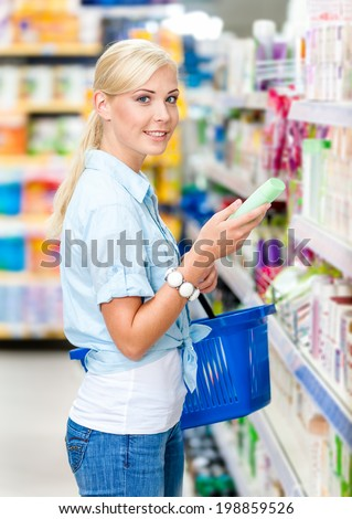 Half length portrait of girl at the market choosing cosmetics among the great variety of products. Concept of consumerism, retail and purchase - stock photo