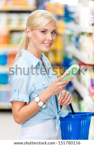 Half length portrait of girl at the store choosing cosmetics among the great variety of products. Concept of consumerism, retail and purchase - stock photo