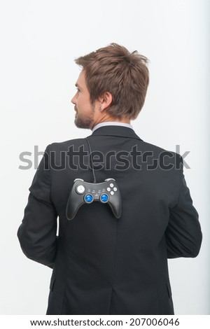 Half-length portrait of handsome businessman in perfect black suit standing back to us and holding the play station on his shoulder - stock photo