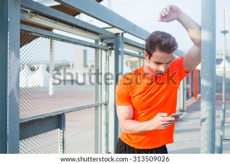Half length portrait of handsome male jogger rest after workout and chat on his mobile phone outdoors in sunny afternoon, young caucasian man using smart phone while taking break after active training - stock photo