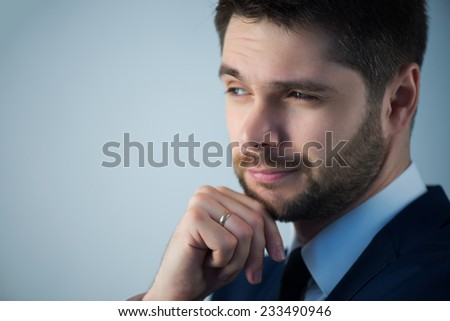 Half-length portrait of handsome young bearded thoughtful man wearing white shirt tie and blue jacket standing aside wanted to remember something. Isolated on white background - stock photo