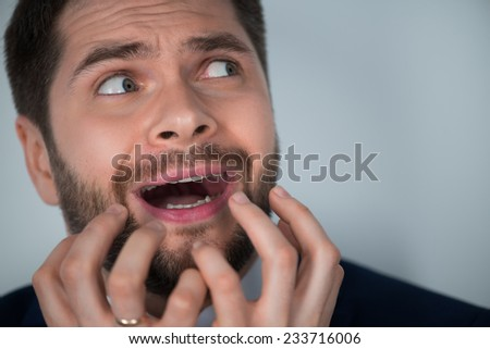 Half-length portrait of handsome young scared man wearing white shirt tie and blue suit crying. Isolated on white background - stock photo