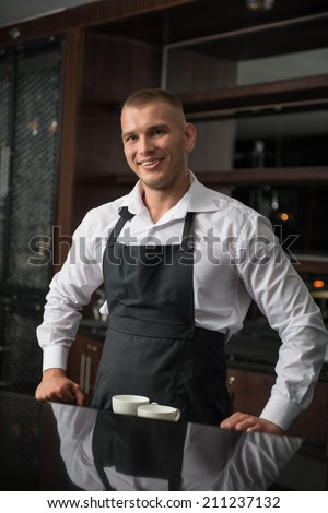 Half-length portrait of handsome young smiling barista wearing white shirt and black apron leaning on the bar counter and looking at us - stock photo