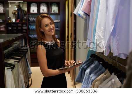 Half length portrait of happy female entrepreneur using digital tablet for job in her modern store with men's clothes, smiling woman owner or consultant holding touch pad while standing in brandy shop - stock photo