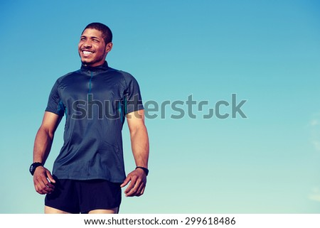 Half length portrait of happy smiling athlete resting after an active workout standing against blue sky background with copy space area for your text message or advertising content, happy male runner - stock photo