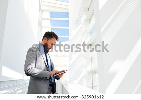 Half length portrait of man managing director dressed in luxury expensive clothes using digital tablet for work, young prosperous male using touch pad while standing in modern office building interior - stock photo
