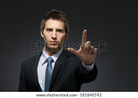 Half-length portrait of manager forefinger gesturing who wears business suit and black tie - stock photo