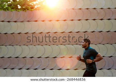 Half length portrait of muscular build sports man running along beautiful wall outdoors, male runner working out outside at amazing sunset light, filtered image, flare sunset light - stock photo