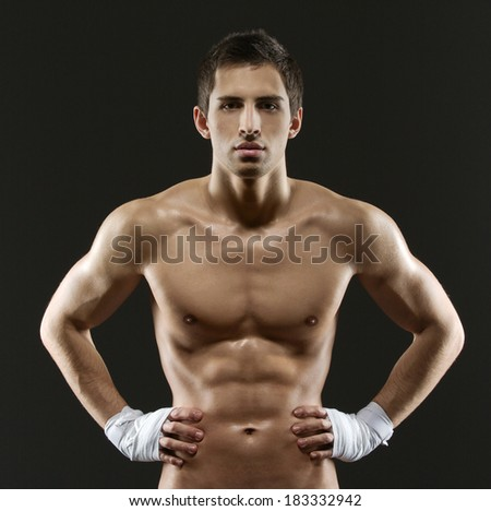 Half-length portrait of nude boxer with hands on hips, isolated on black - stock photo