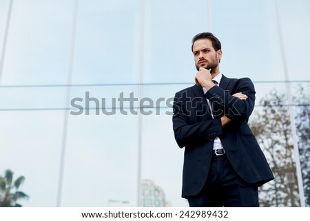 Half length portrait of pensive young businessman standing against office building - stock photo