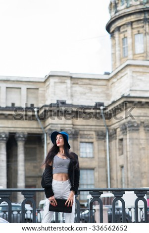 Half length portrait of pretty elegant woman standing near the vintage building and looking aside, charming woman dressed in stylish clothes rest after strolling in urban setting during weekends - stock photo