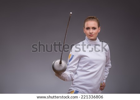 Half-length portrait of pretty smiling girl wearing fencing costume practicing in fencing with her rapier. Isolated on dark background - stock photo