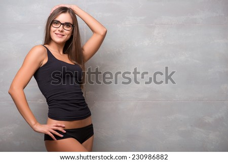 Half-length portrait of sexy smiling dark -haired young woman in nice eyeglasses wearing black vest and shorts standing aside showing her perfect figure - stock photo