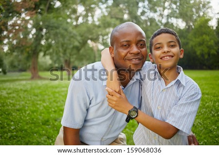 Half-length portrait of smiling african father and son standing embraced  in summer park - stock photo