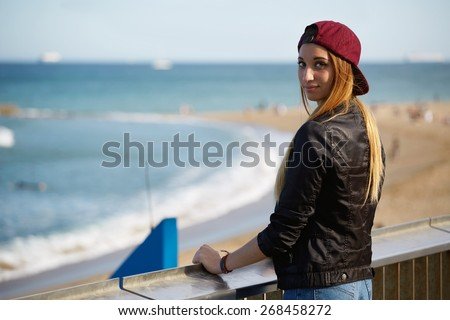 Half length portrait of stylish hipster girl standing on the pier of beautiful beach, young woman enjoying beautiful afternoon outdoors with blue sea on background, promenade at sunny day - stock photo