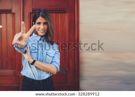 Half length portrait of the beautiful young woman standing at the wooden door background smiling, positive hipster girl showing peace with copy space area for your text message or advertising content - stock photo