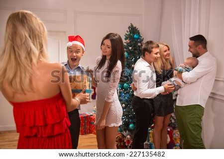 Half-length portrait of the company of happy smartly-dressed people standing in the big light cozy room with the nice New Year tree in the corner greeting each other with the holiday giving trimming - stock photo