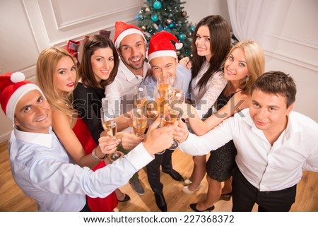 Half-length portrait of the company of happy young smiling friends standing together drinking the champagne greeting us with the New Year. Top view - stock photo