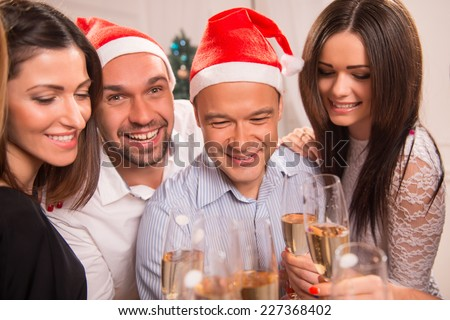 Half-length portrait of the company of happy young smiling friends standing together drinking the champagne greeting each other with the New Year - stock photo