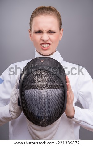 Half-length portrait of the fair-haired angry girl wearing white fencing costume holding the fencing mask in front of her. Isolated on grey background - stock photo