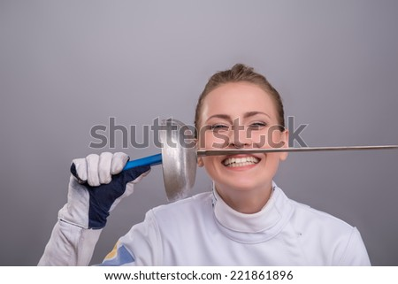 Half-length portrait of the fair-haired pretty smiling girl wearing white fencing costume holding her sword near her lips and looking at us. Isolated on grey background - stock photo