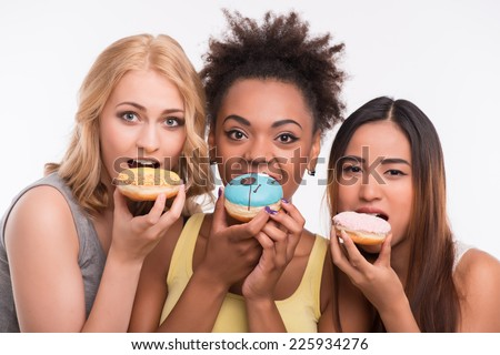 Half-length portrait of three beautiful tempting girls wearing colorful T-shirts eating bright delicious doughnuts. Isolated on white background - stock photo
