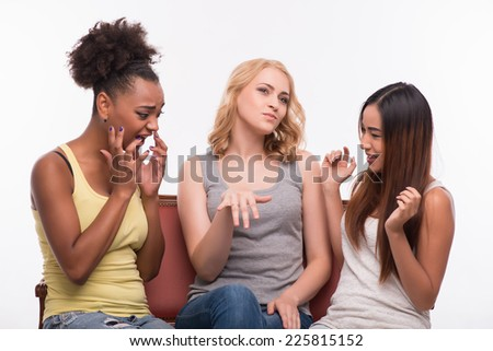 Half-length portrait of three pretty smiling girls wearing jeans and T-shirts sitting on the sofa discussing the engagement of one of them. Isolated on white background - stock photo