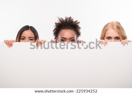 Half-length portrait of three young lovely smiling girls wearing colorful T-shirts and jeans looking out of the big white poster for copy place. Isolated on white background