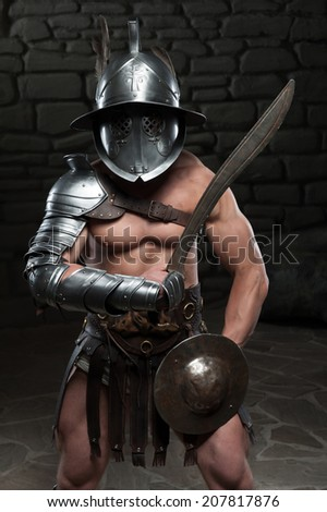 Half length portrait of warrior gladiator with muscular body in helmet holding sword on dark background. Concept of masculine power, strength - stock photo