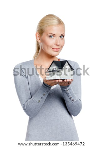 Half-length portrait of woman in grey pullover with small model house, isolated on white - stock photo