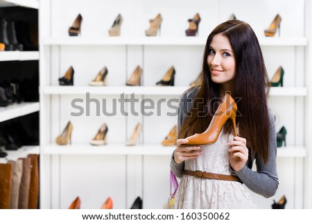 Half-length portrait of woman keeping brown leather high heeled shoe in shopping center - stock photo